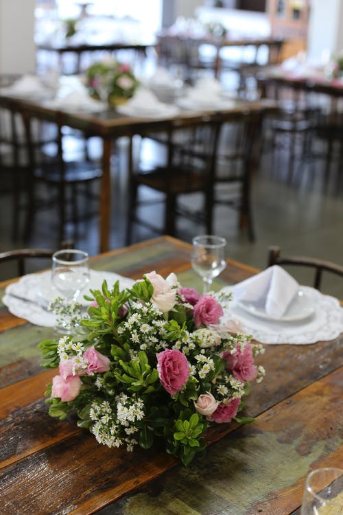 Pink And White Flower Centerpiece Beside Wine Glasses And Plates On Brown Table