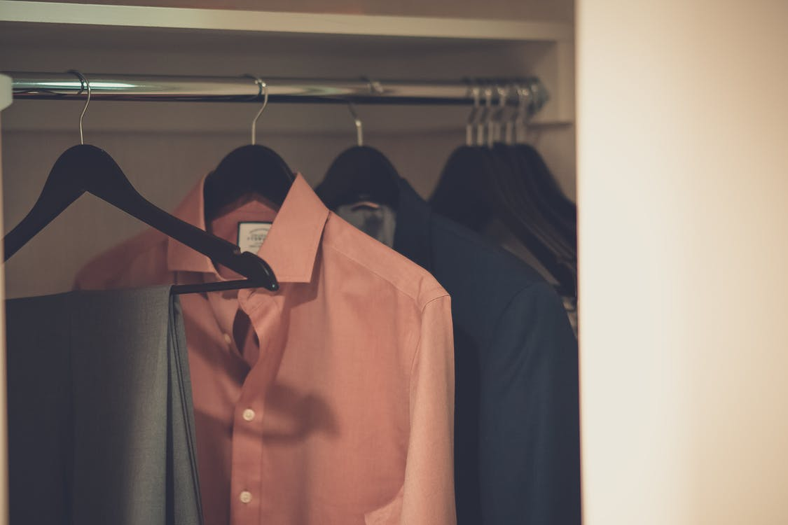Close-up Photo of Hang Clothes in Wardrobe