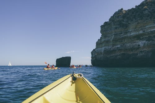 Photo of People Kayaking Near Rock Formation