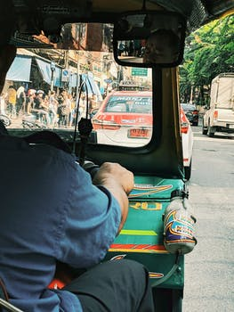 close up of man driving tuk tuk
