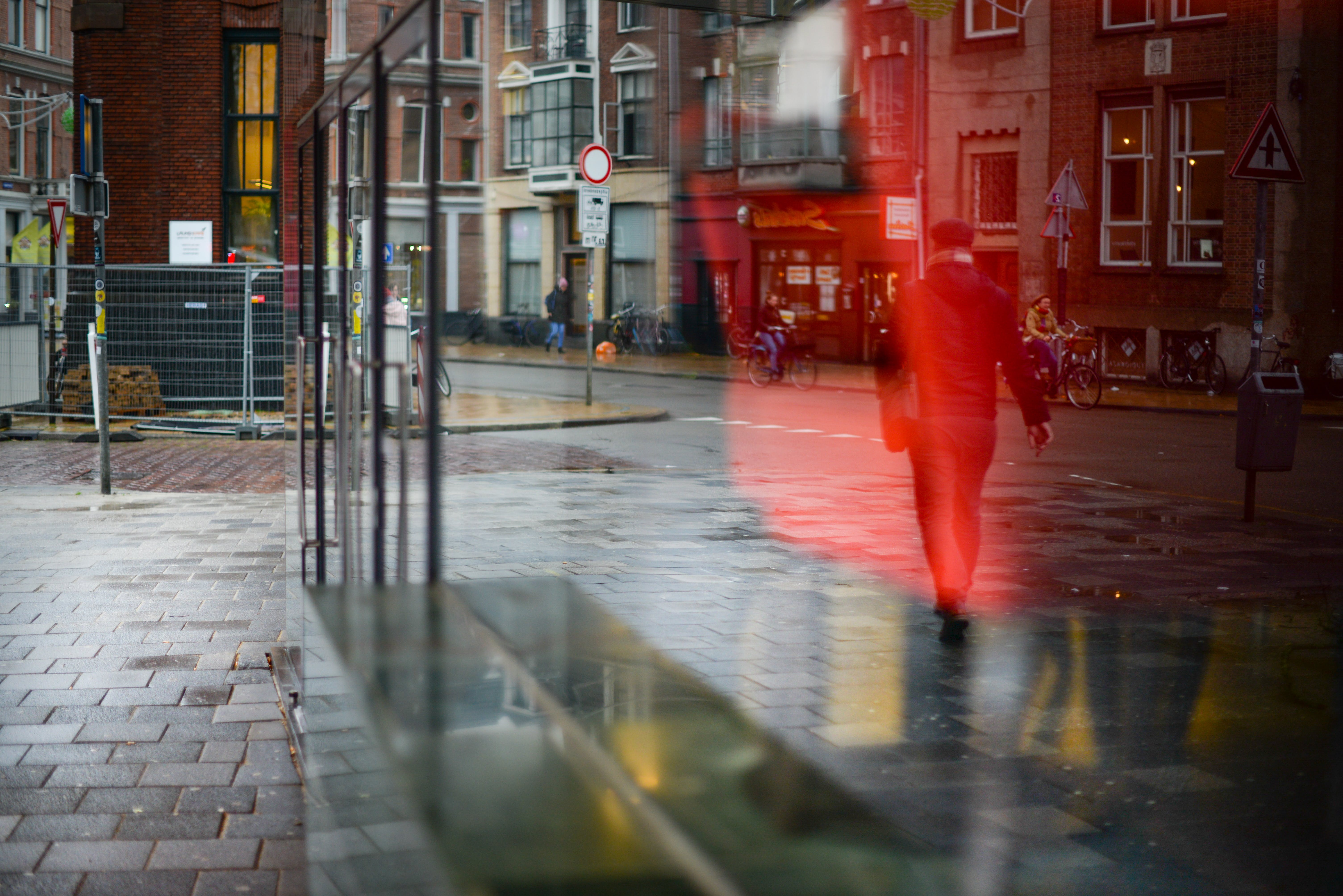 Man Walking on Road Reflected on Glass Window