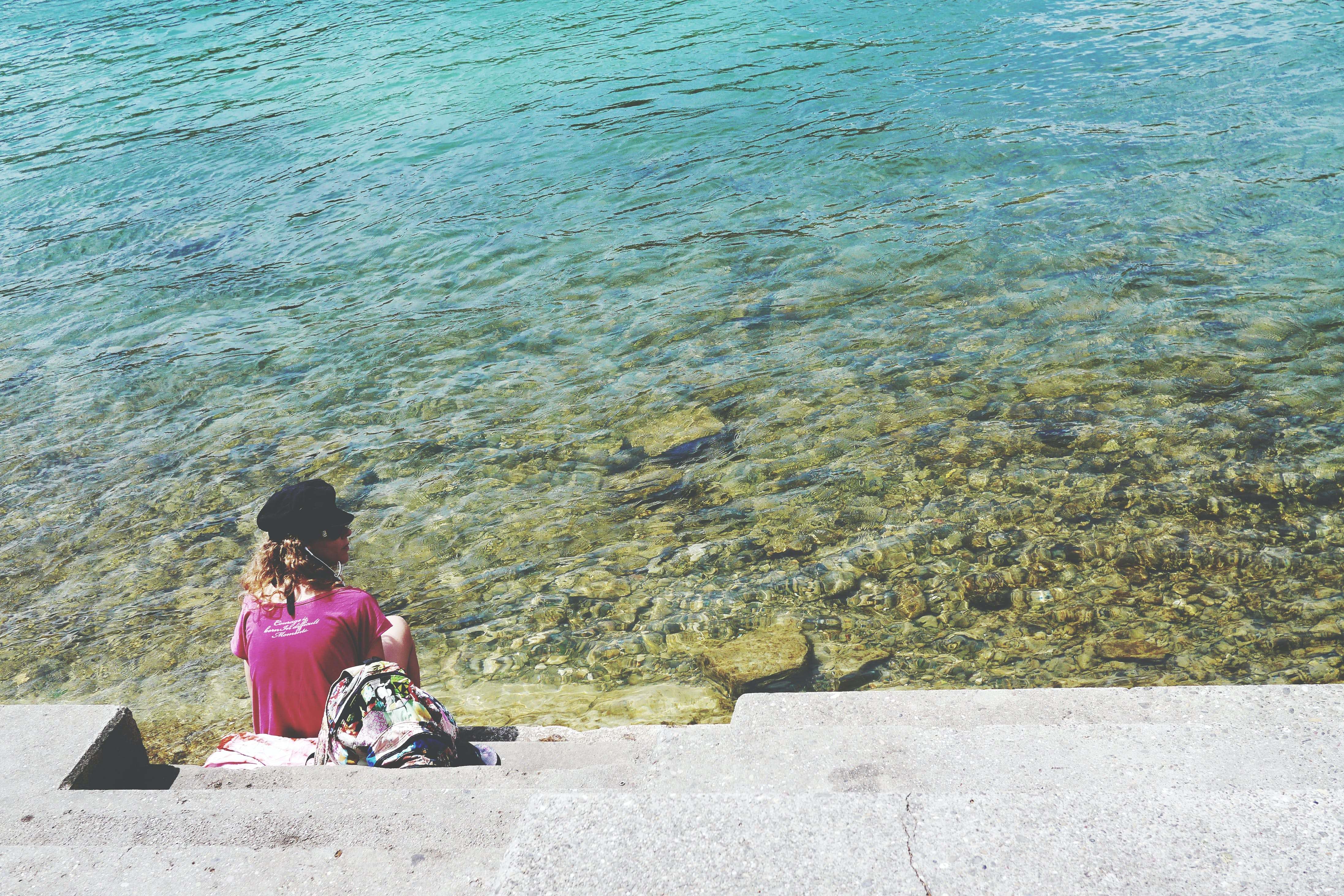 Woman Sitting in Front of Sea during Daytime