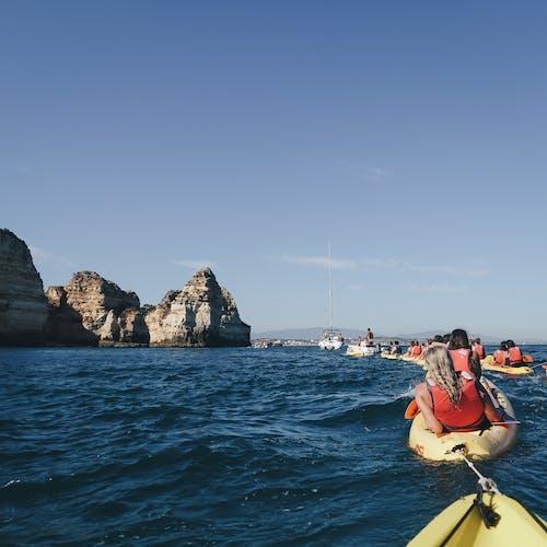 People Kayaking During Day