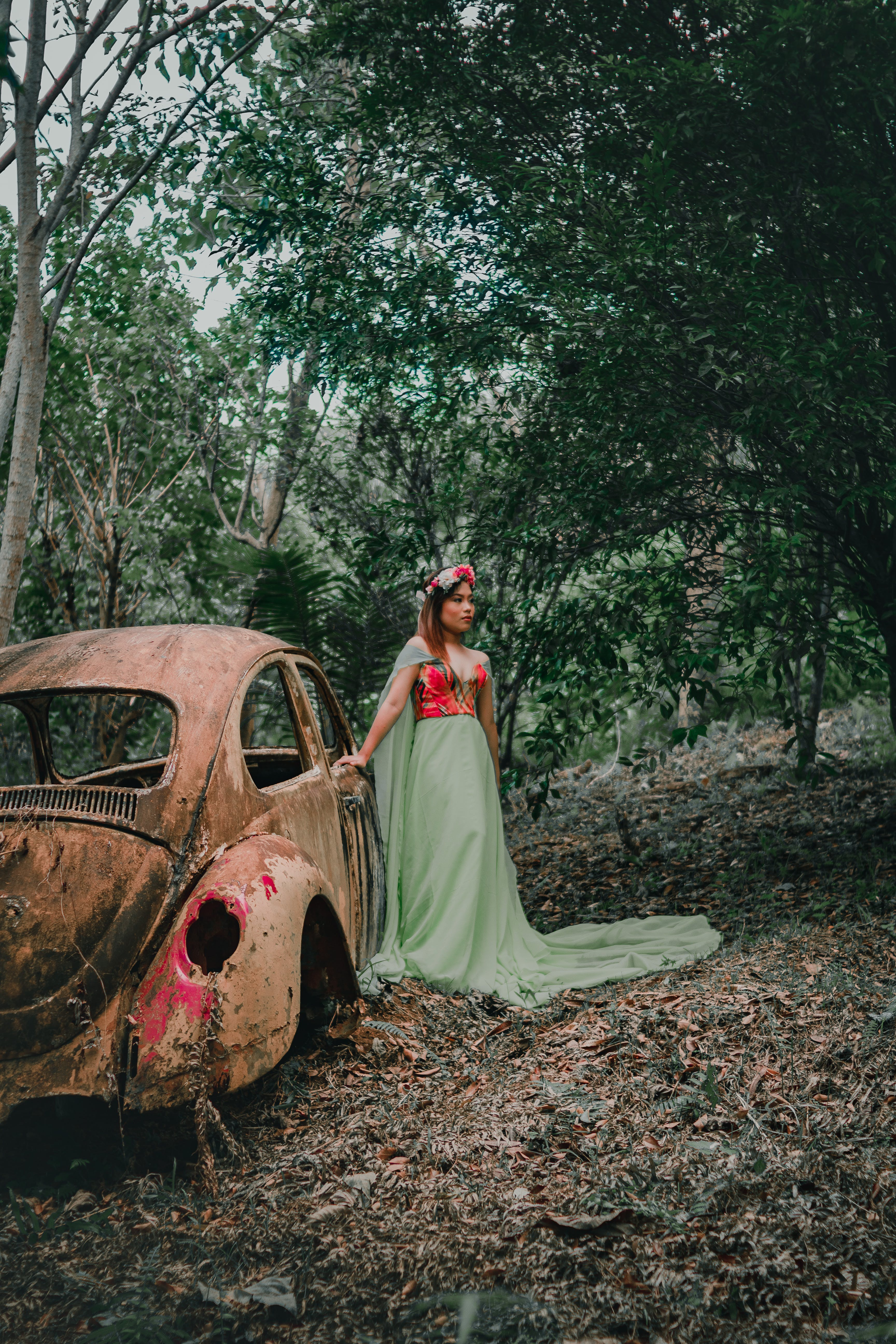 Woman Wearing Green and Red Dress Standing Beside Rusted Brown Volkswagen Beetle Coupe Surrounded by Trees