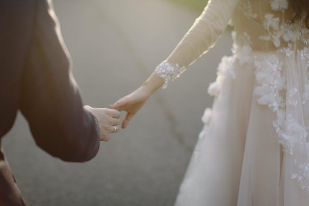 Newlyweds holding hands. | Photo: Pexels