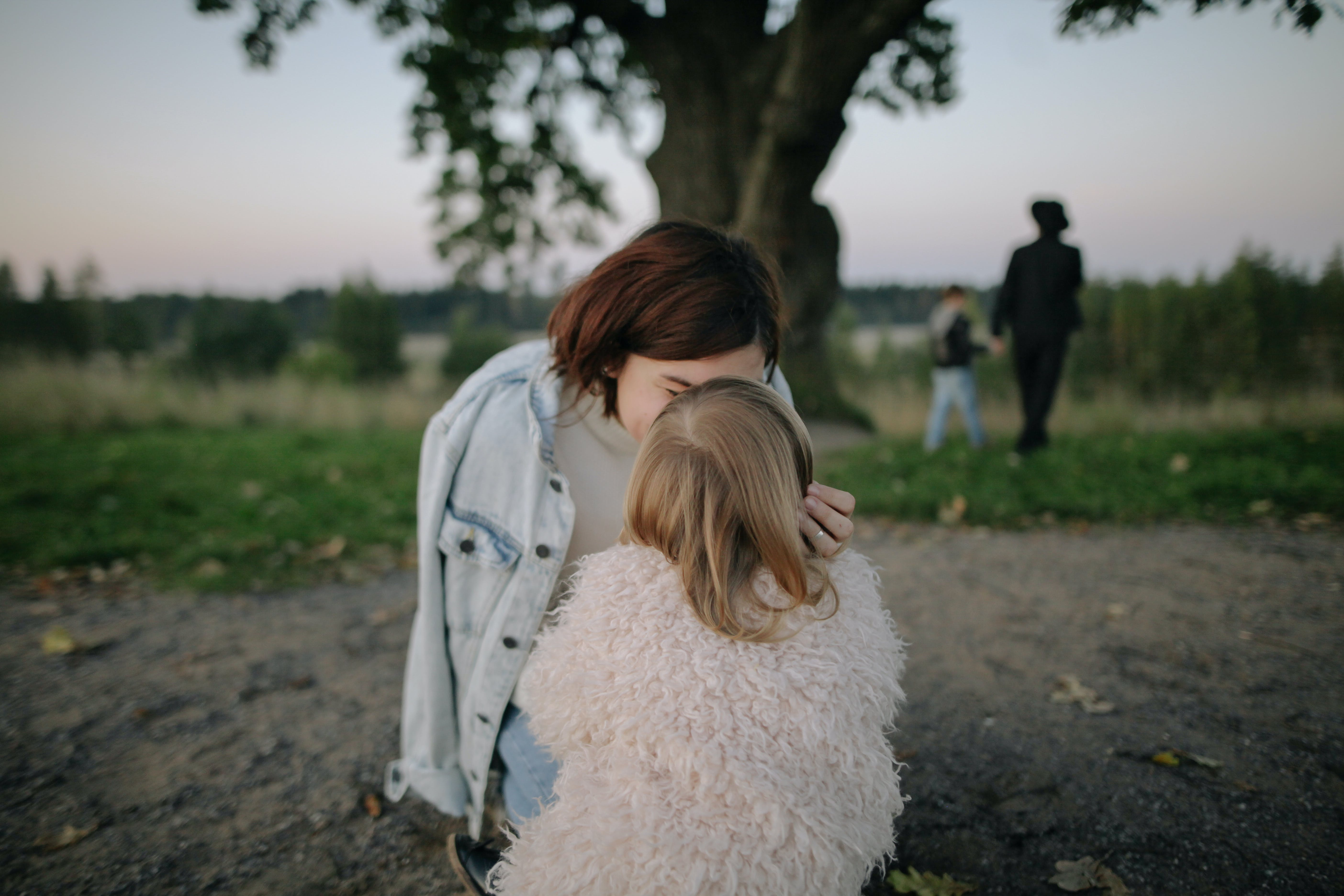 Woman Wearing Light-blue Denim Jacket Kissing Girl Wearing White Coat