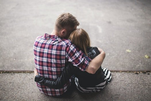 Man in Red White and Blue Check Long Sleeve Shirt Beside Woman in Black and White Stripes Shirt Hugging Each Other While Sitting on a Concrete Surface