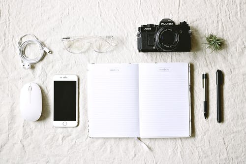 White Notebook Beside Pens and Gold Iphone 6 and Camera