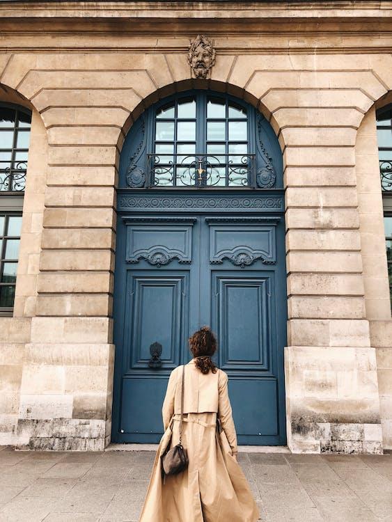 Woman in Beige Coat Standing in Front of Blue Wooden Door