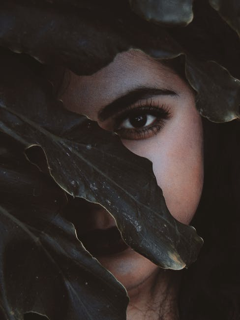 Woman's Face Behind the Leaf Close-up Photo
