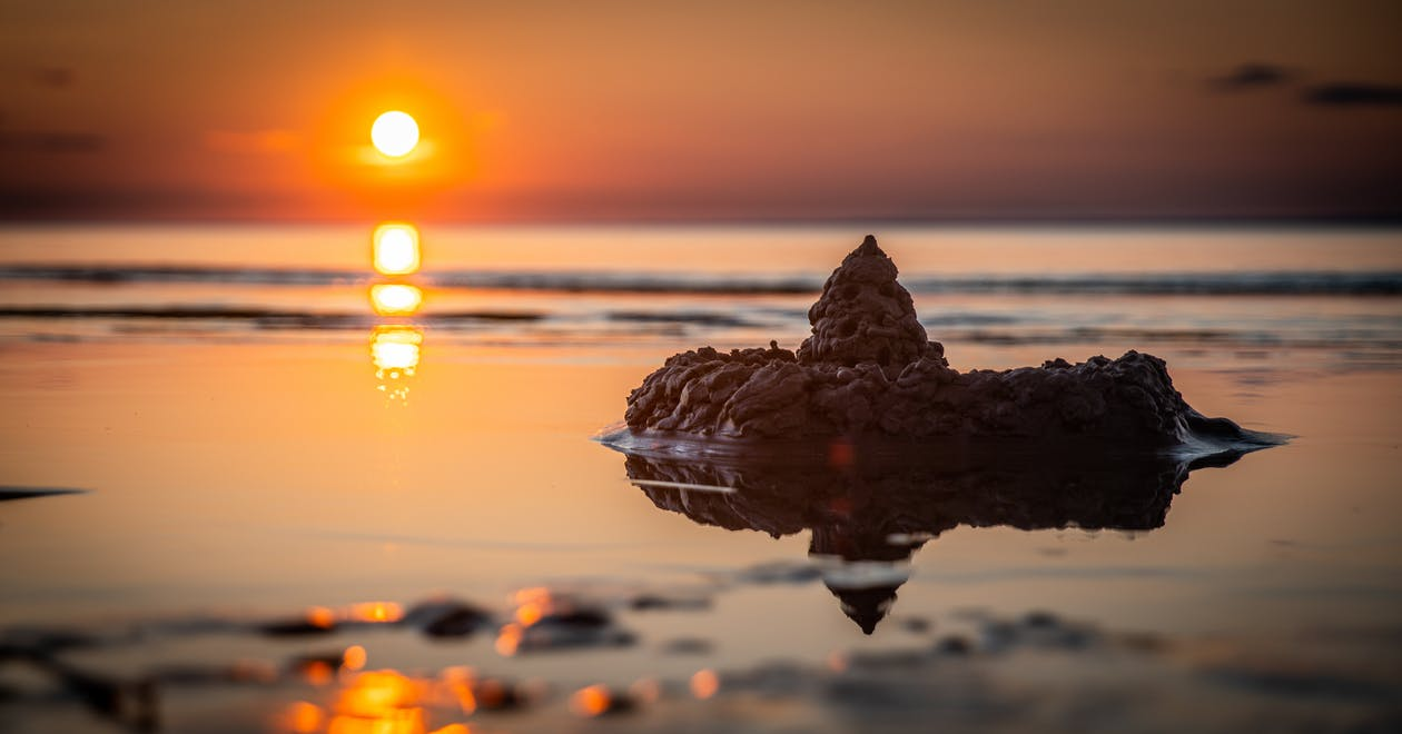 Sand Castle on Seashore during Golden Hour