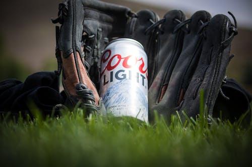 검은 야구 장갑 근처 쿠어스 라이트 맥주의 사진을 닫습니다