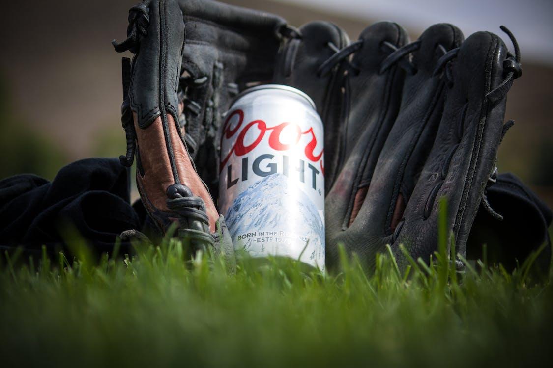 Fotografía De Cerca De Cerveza Ligera Coors Cerca De Guantes De Béisbol Negros