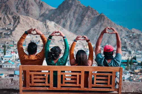 Four People Making Heart Hand Sign While Sitting