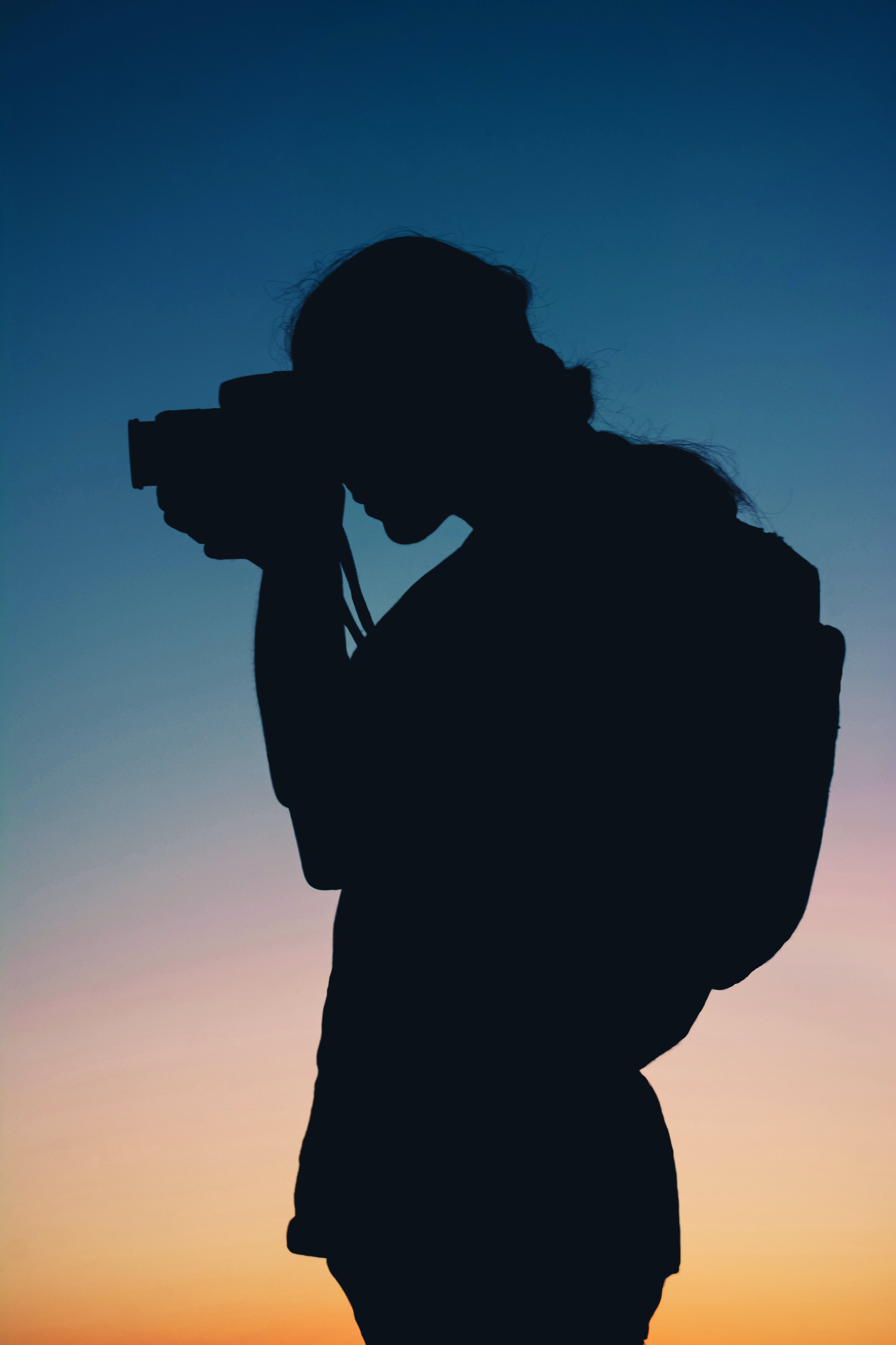 Silhouette of Person Taking Photo With Camera
