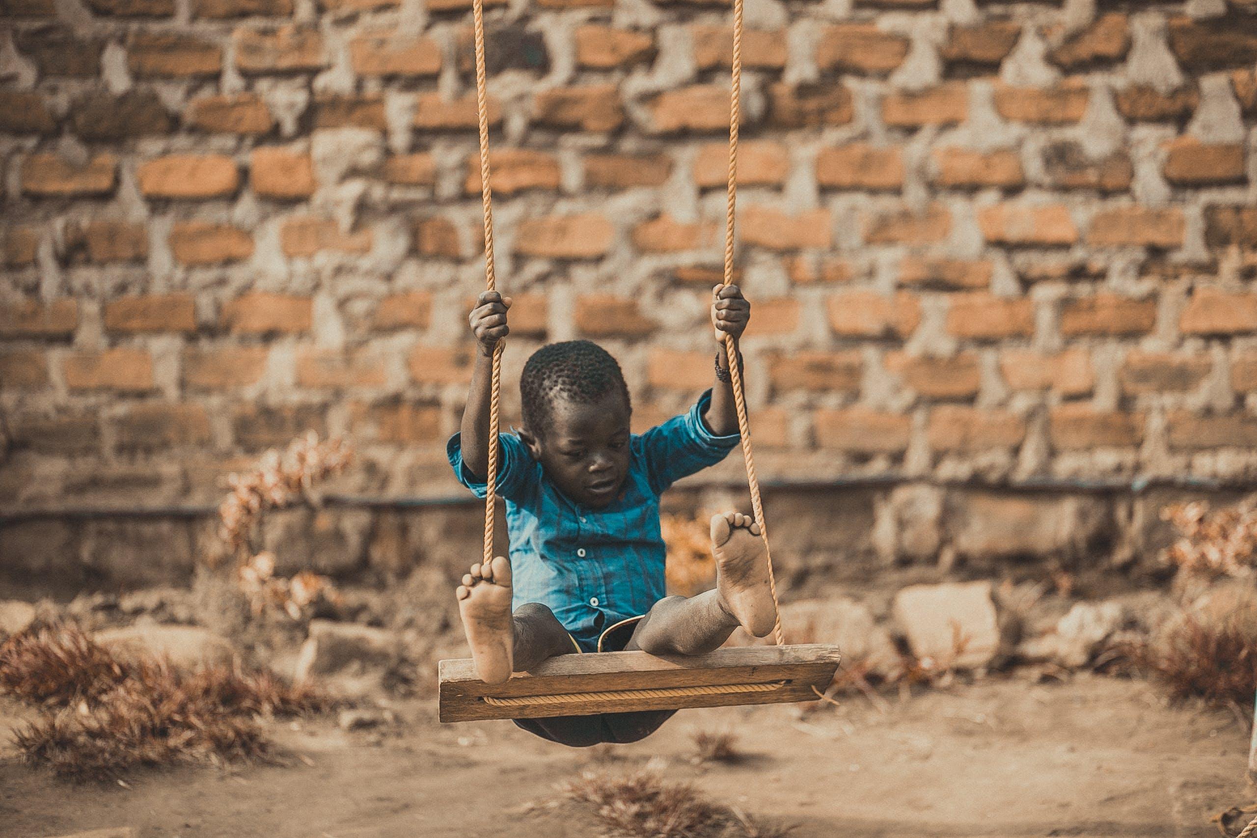 Gratis stockfoto met Afrika, Afrikaanse jongen, bakstenen muur, blijdschap