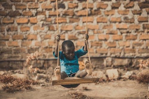 Kostenloses Stock Foto zu afrika, afrikanischer junge, backsteinmauer, glück