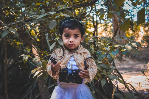 Photo of Small Girl Holding Camera