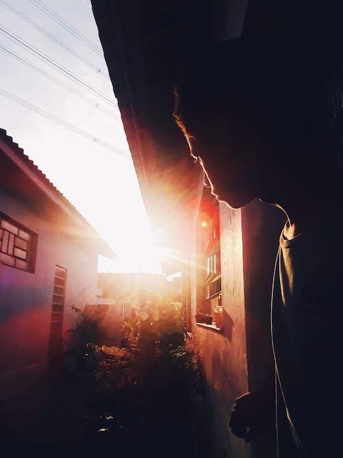 Man Standing on Door With Sun Reflect