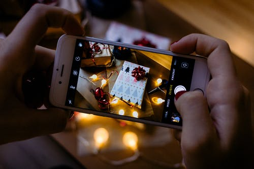 Person Using Iphone Taking Picture of Gift Box