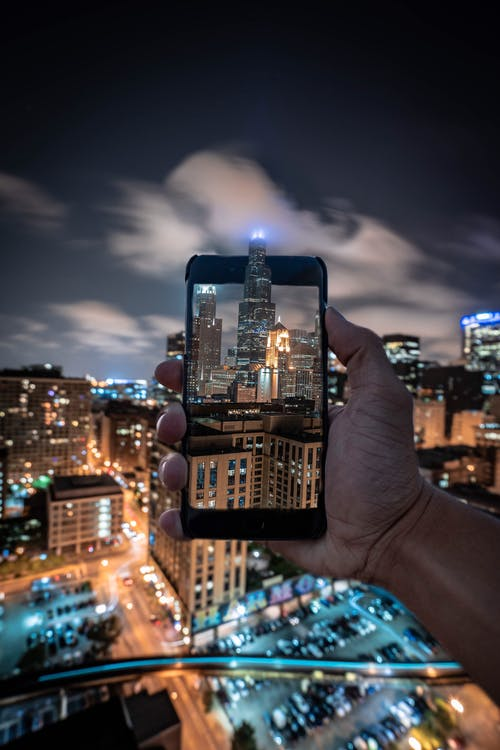 Person Taking Photo of Skyscraper