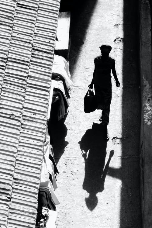 Silhouette Photography of Person Waling on Street