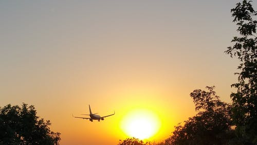White Airplane in Mid Air during Yellow Sunset