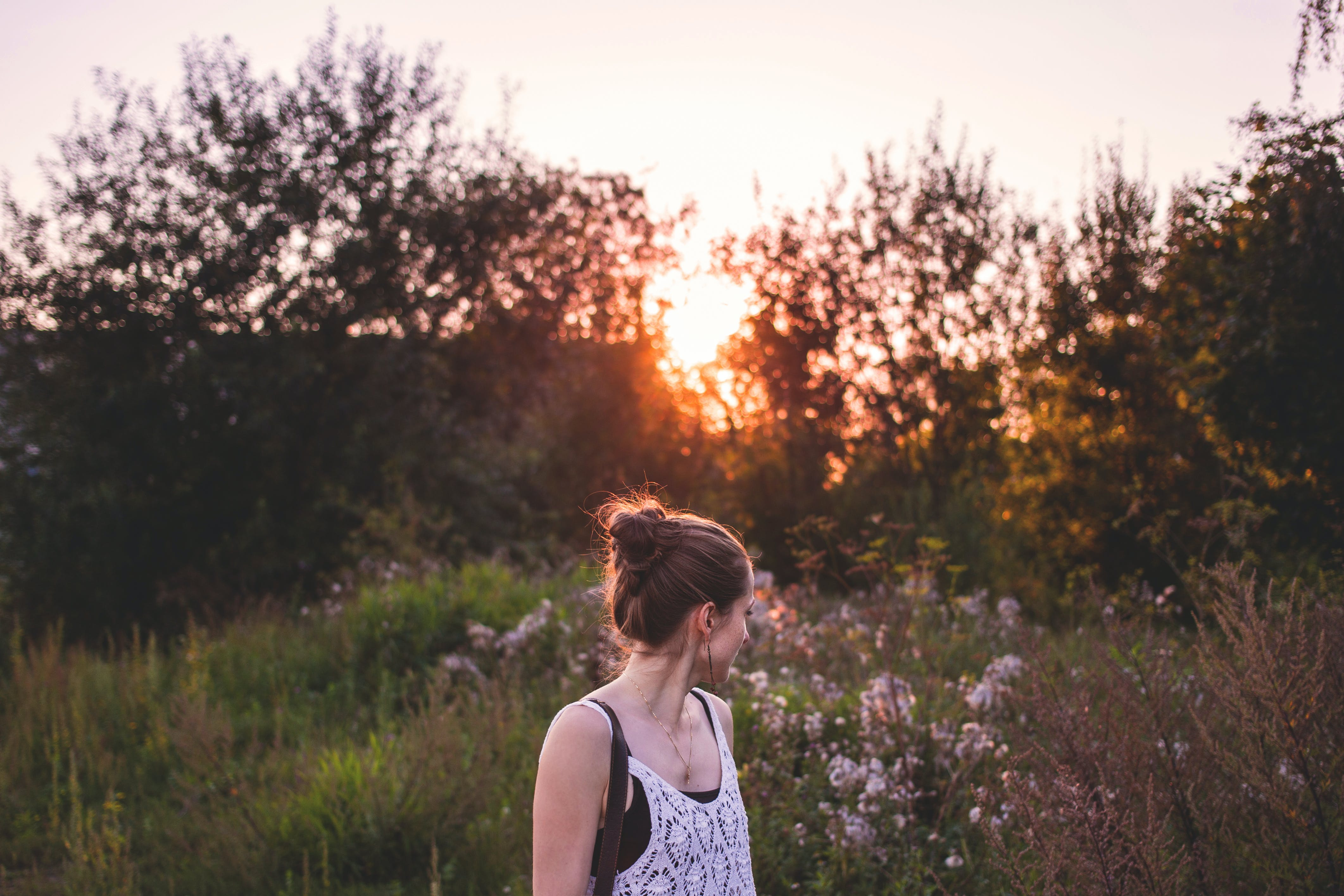 Selective Focus Photography of Woman Standing in the Middle of Grasses and Flowers during Golden Hour
