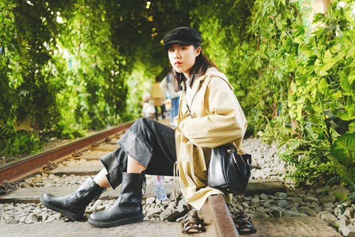 Woman Sitting on Brown Train Rail Near Green Trees