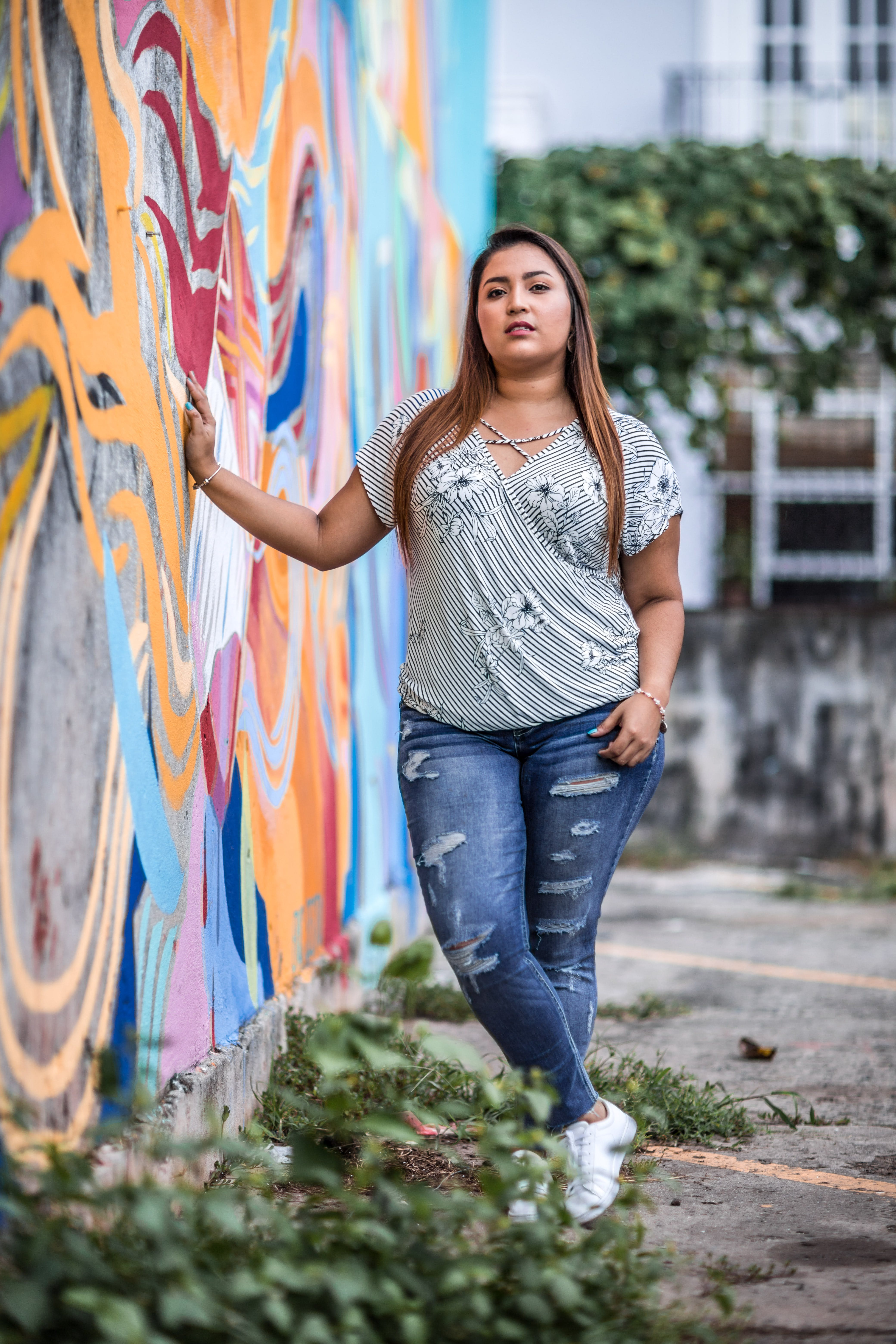 Woman Standing While Holding Multicolored Concrete Wall