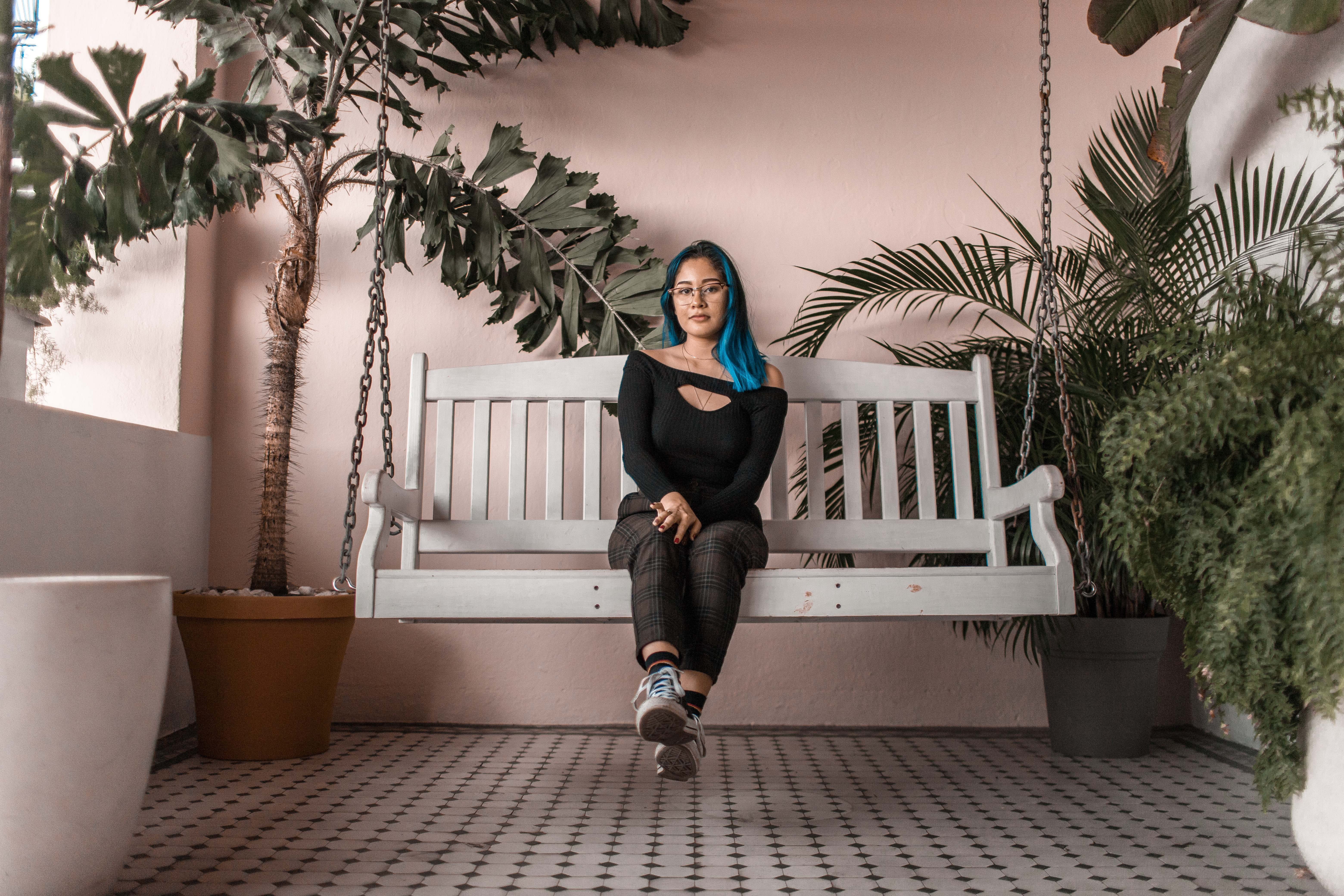 Woman Sitting On Swing Bench