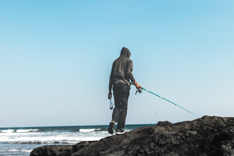 Person Fishing on Seashore