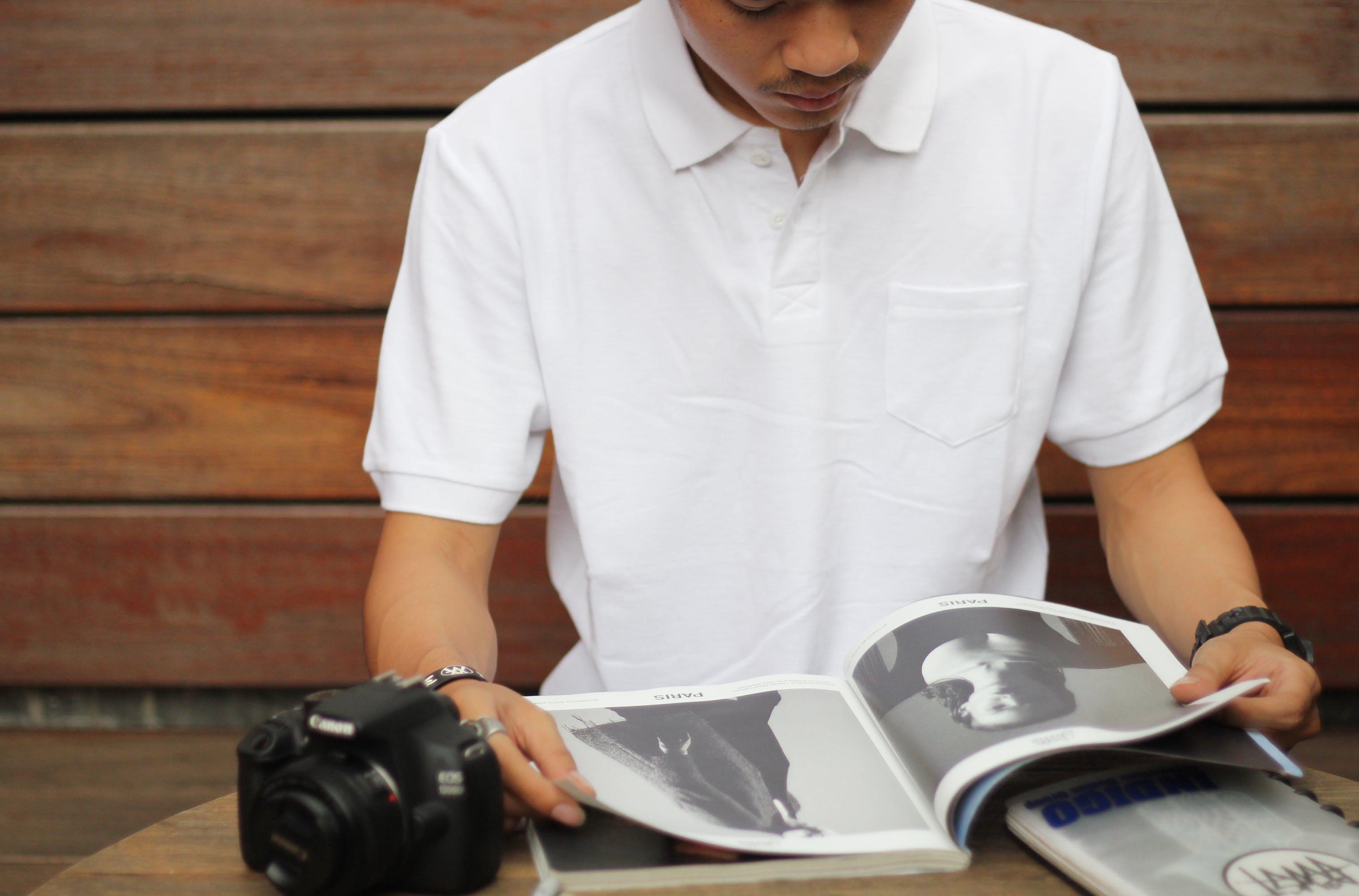 Man Reading Magazine Beside Black Canon Dslr Camera