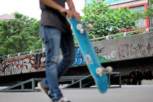 Man Holding Teal Skateboard