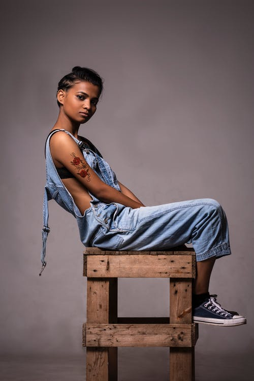 Woman Wearing Dungarees Sitting On Wooden Stool