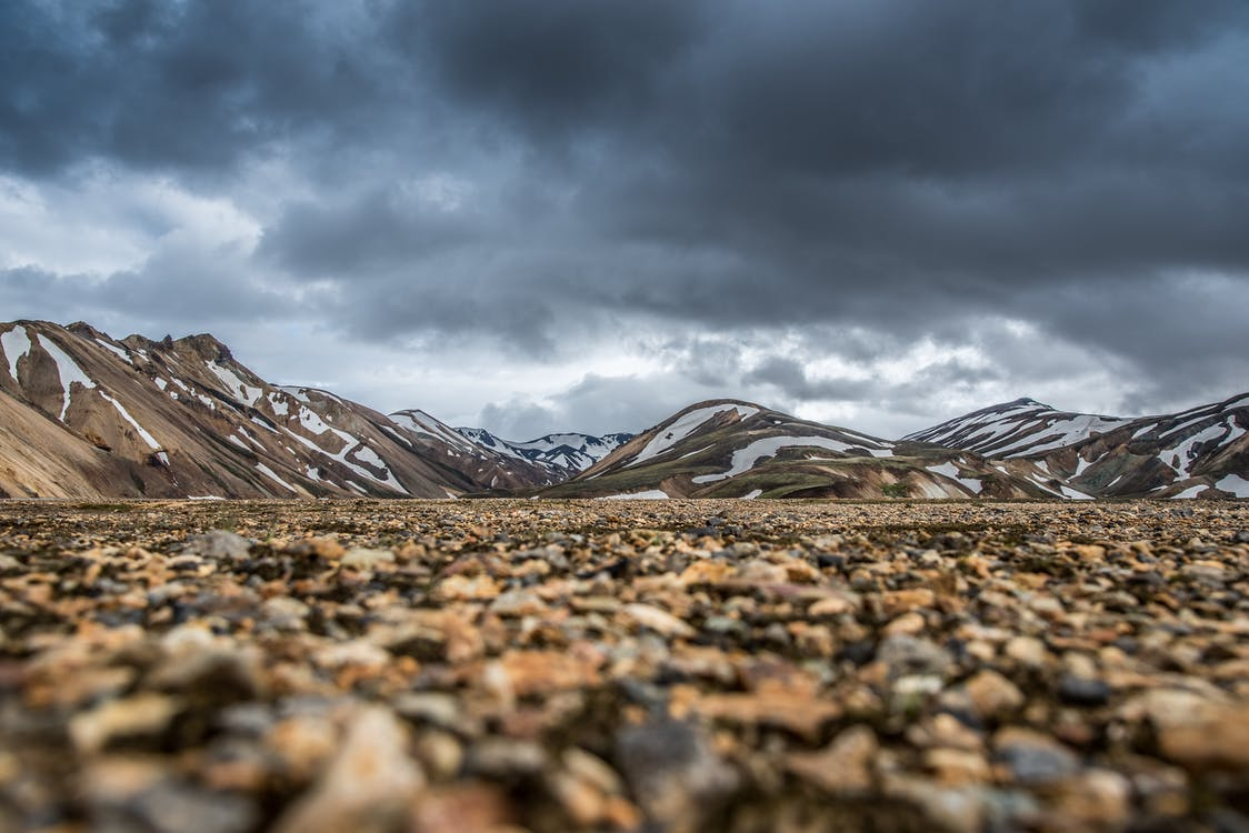 Brown Field Near Mountain Under Cloudy Sky