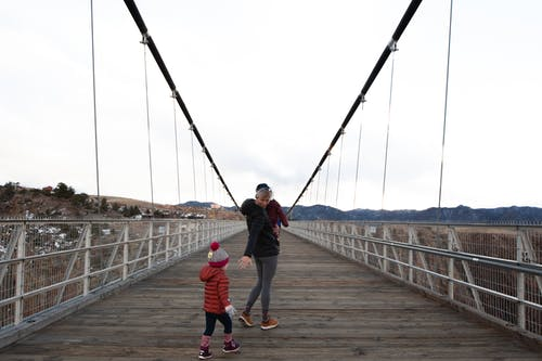 Woman Carrying Child Walking Along Bridge