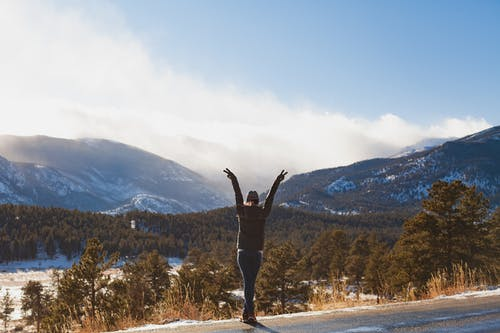 Person Raising Hands on Road Across Mountain Range