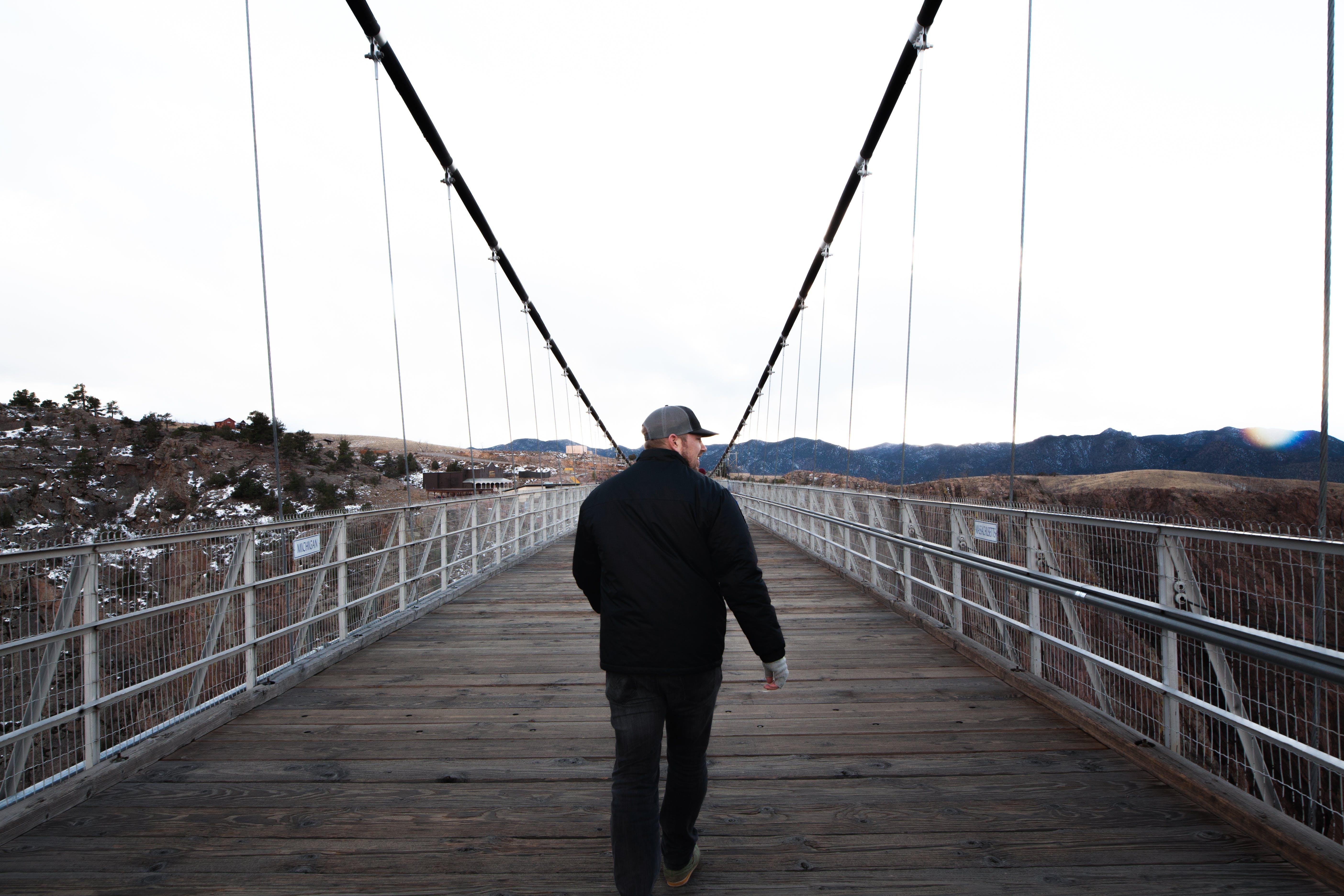 Man Wearing Cap Walking Along Bridge