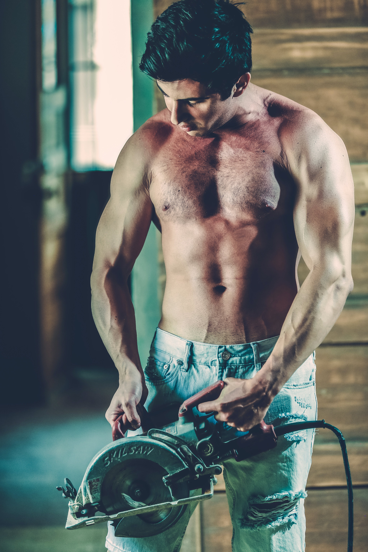 Topless Man Holding Gray Circular Saw