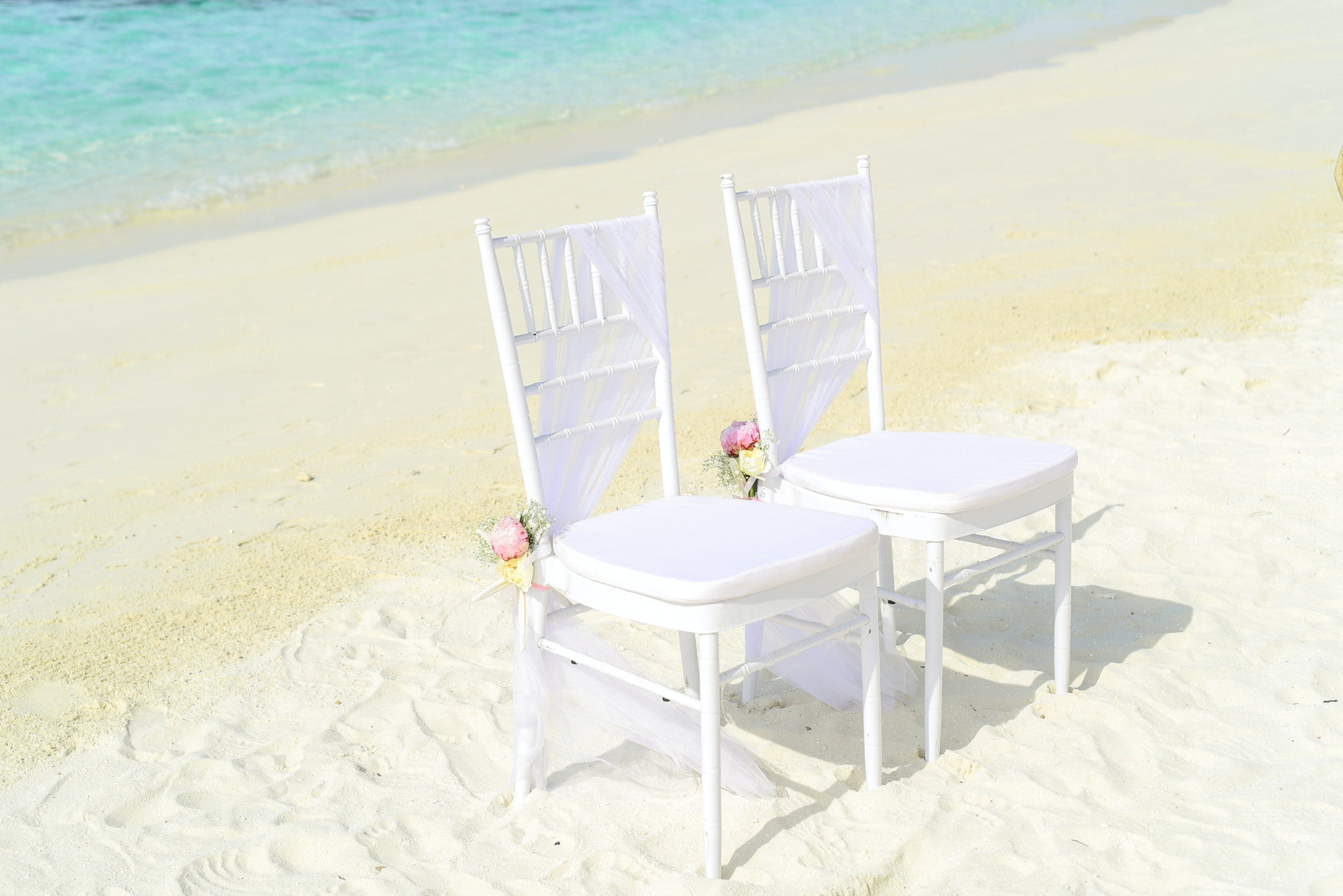 Two White Armless Chairs on Seashore