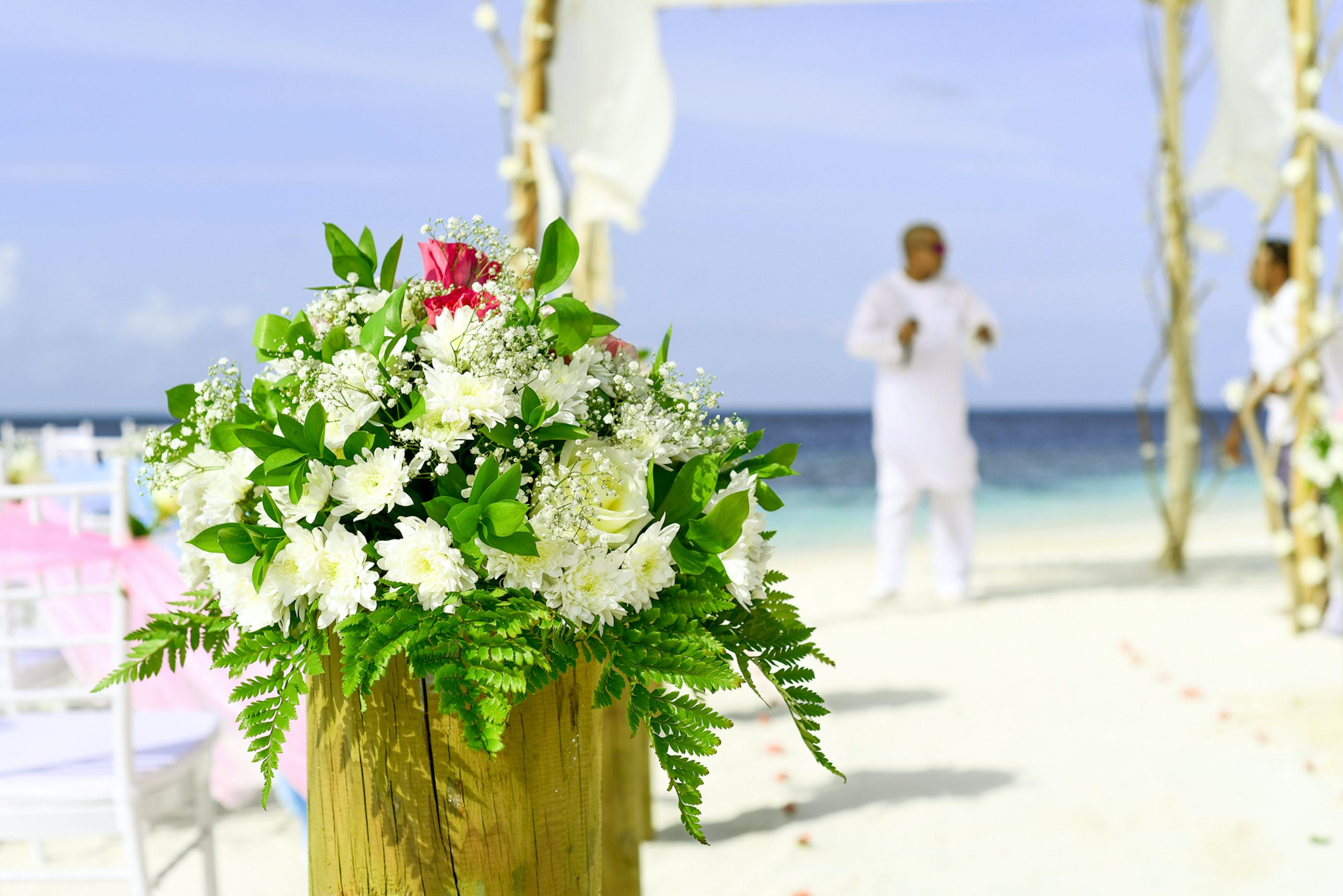 Selective Focus Photography of White Chrysanthemum Flowers Bouquet Near Man in White Thobe on Seashore