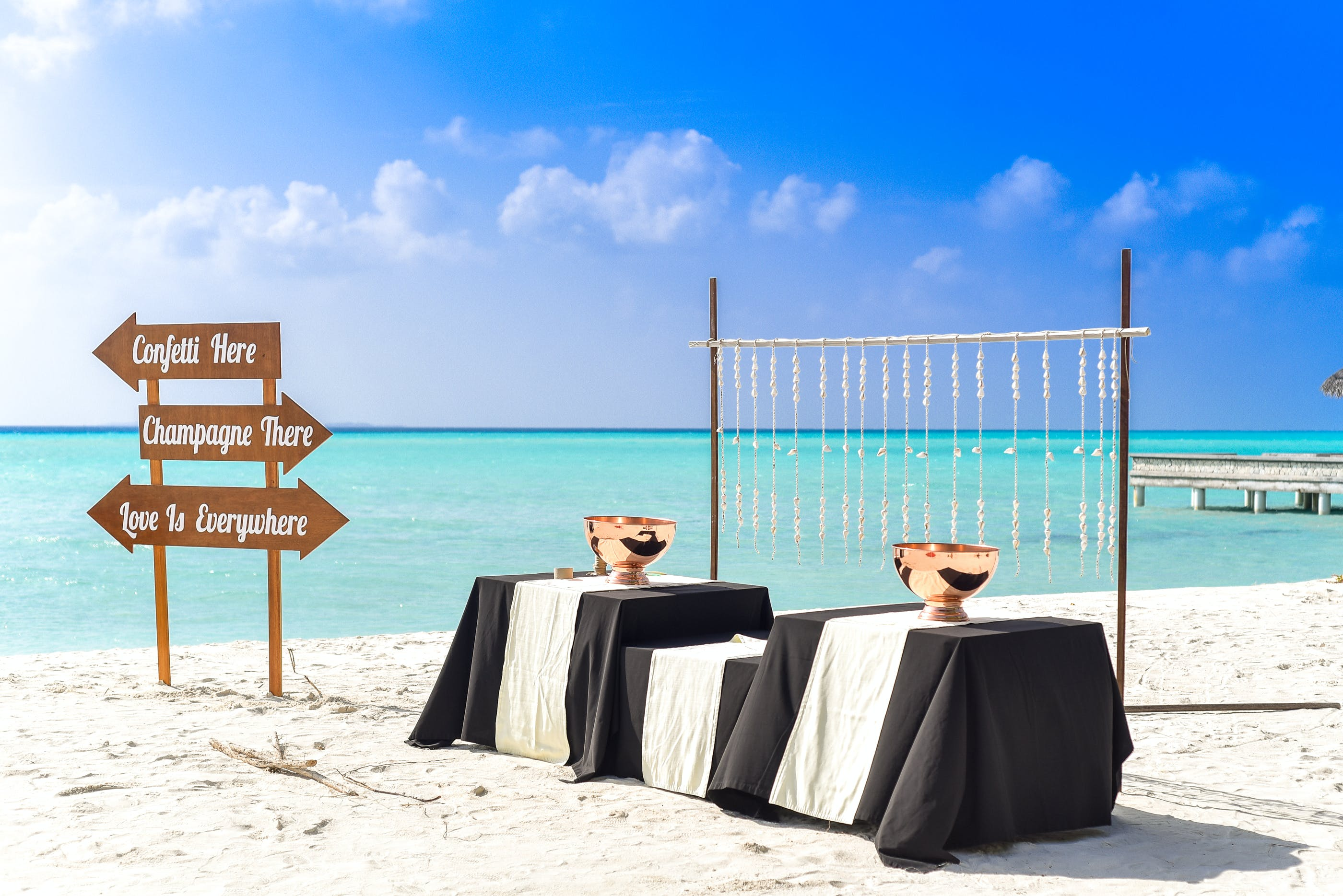Three Tables Covered With Black and White Tablecloths on Seashore