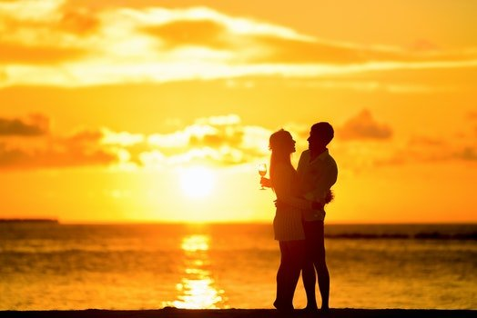 Couple Standing in the Seashore Hugging Each Other during Sunset