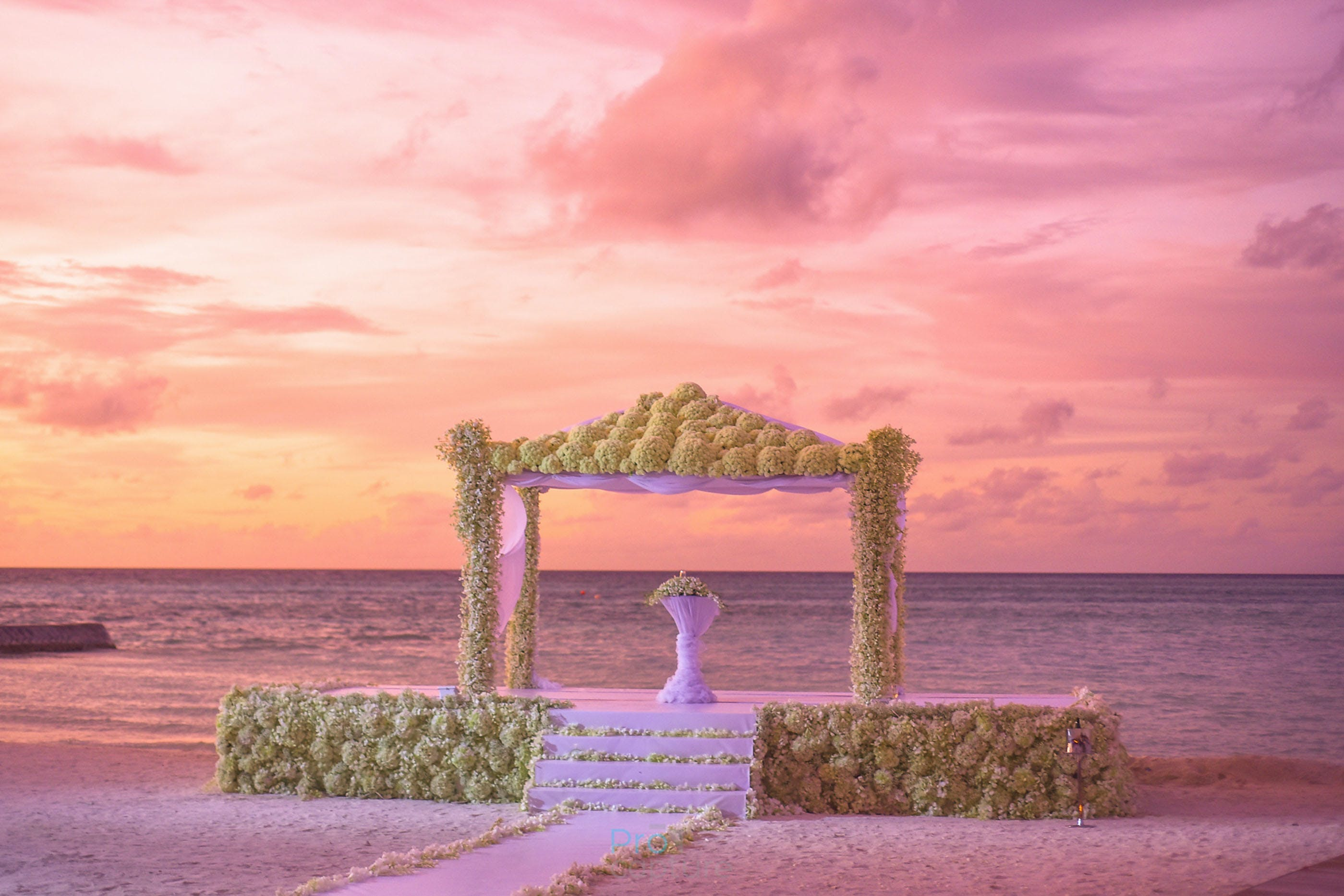 White Table Under Brown Concrete Gazebo Along Body of Water Under White Orange and Pink Cloudy Sky during Sunset