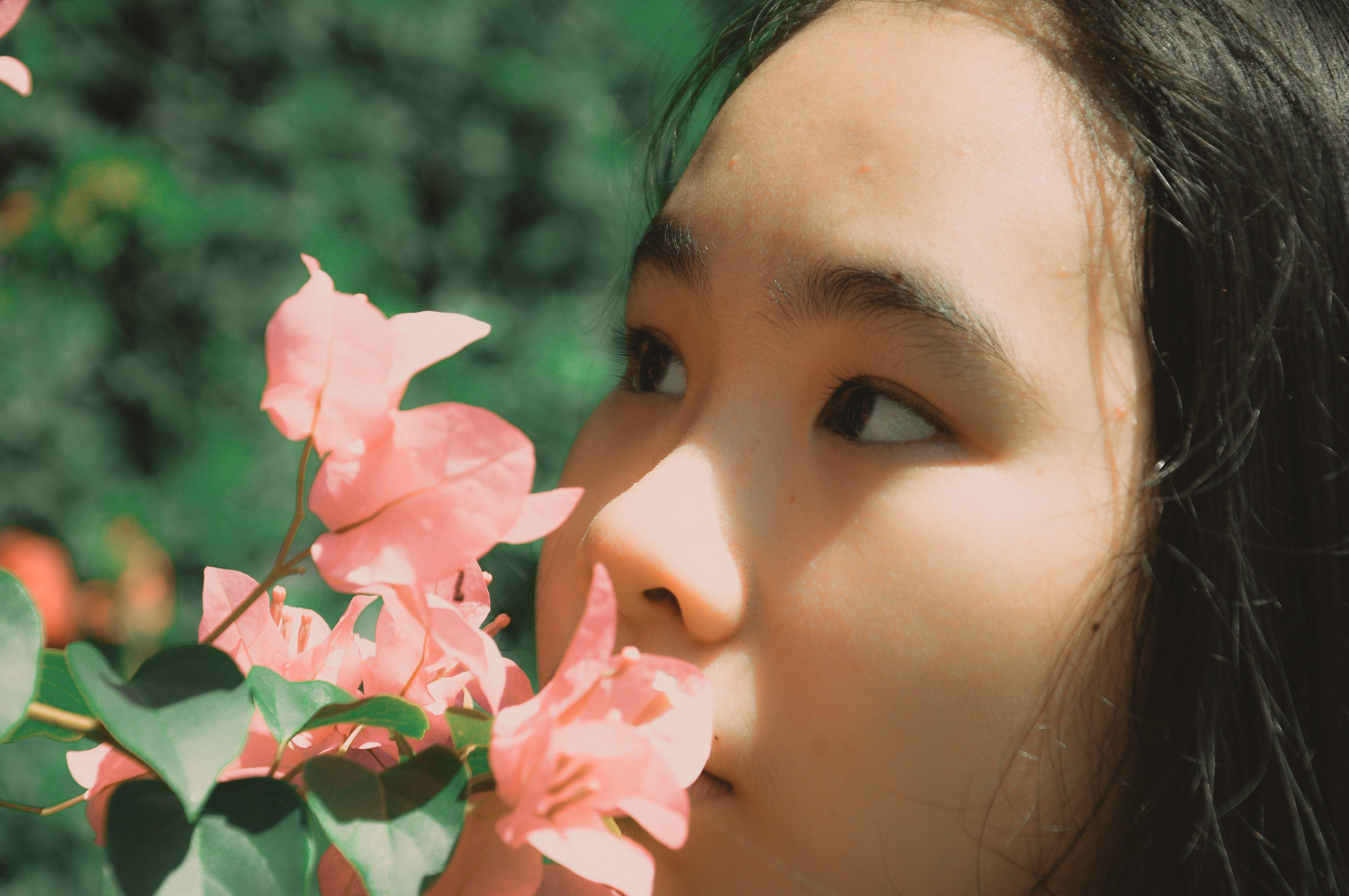 Woman Smelling Pink Bougainvillea Flower