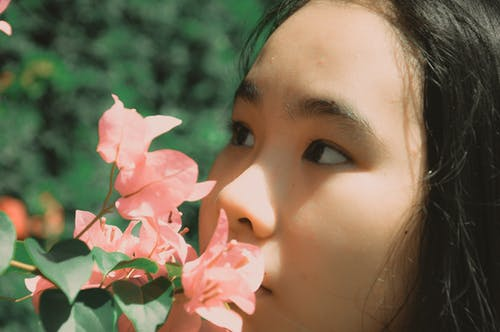 Woman Smelling Pink Bougainvillea Flower