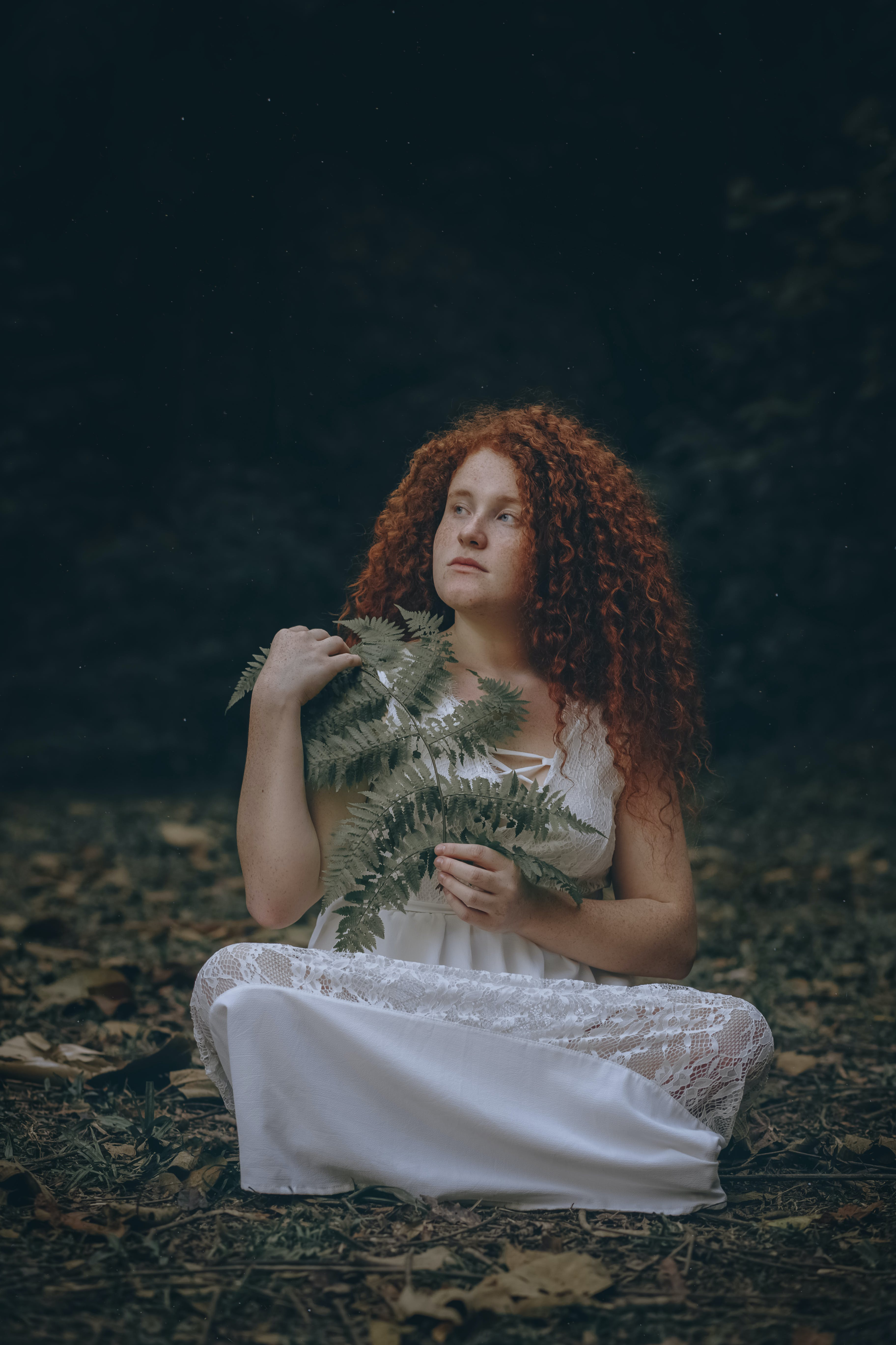 Photo of Woman Sitting While Holding Green Leaves