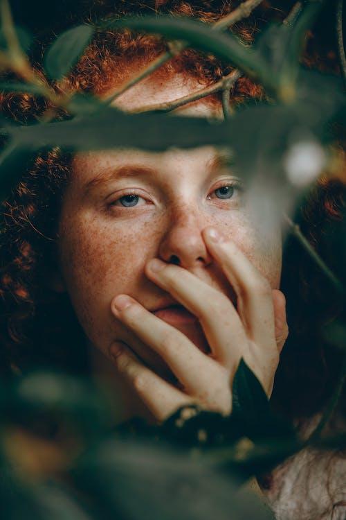 Femme Tenant Son Visage à Côté De Plantes à Feuilles Vertes