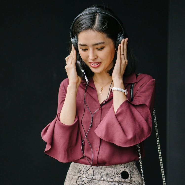 Woman Holding Black Wired Headphones